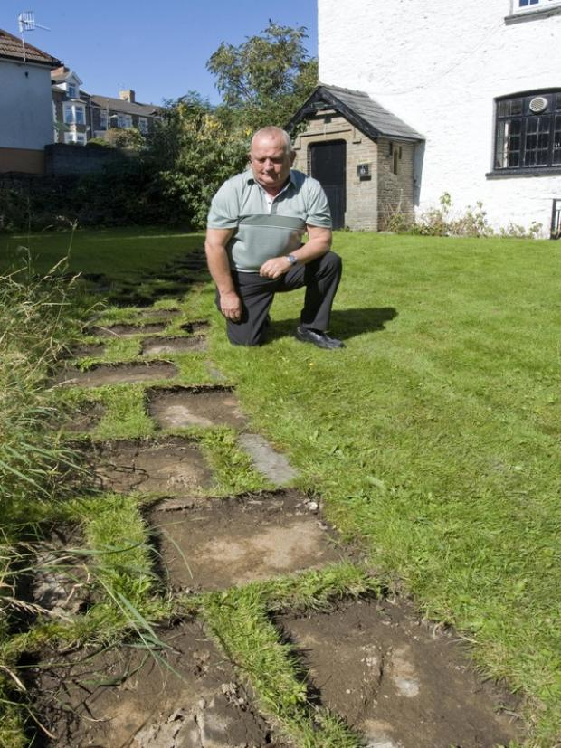 Bargoed RAFA Club Treasurer Mike Davies looks at the muddy path remaining now the slabs have been stolen.