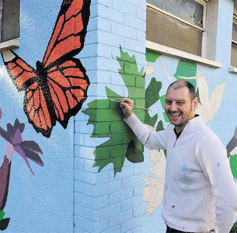 FLUSH FINISH: Artist Craig Lewis works on the mural