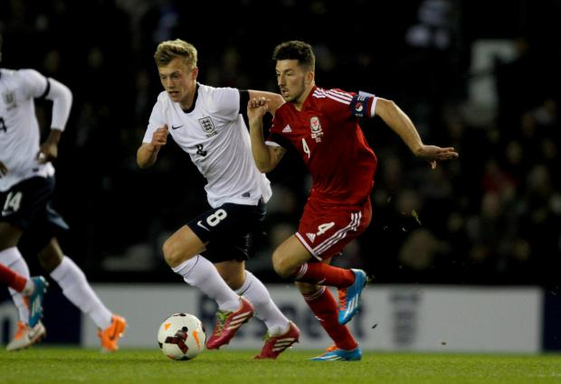 BATTLE: Wales skipper Lee Lucas gets away from England's James Ward-Prowse