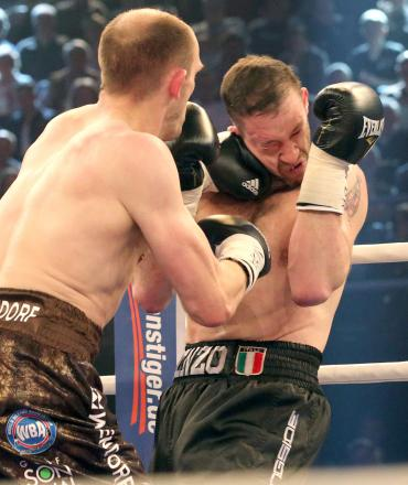 In this picture taken Saturday  April 5, 2014, German  WBA  light heavyweight boxer Juergen Braehmer, left,  lands a punch on  Enzo Maccarinelli of Wales  in Rostock, northeastern Germany.  Juergen Braehmer of Germany defeated Enzo Maccarinelli of Wales b
