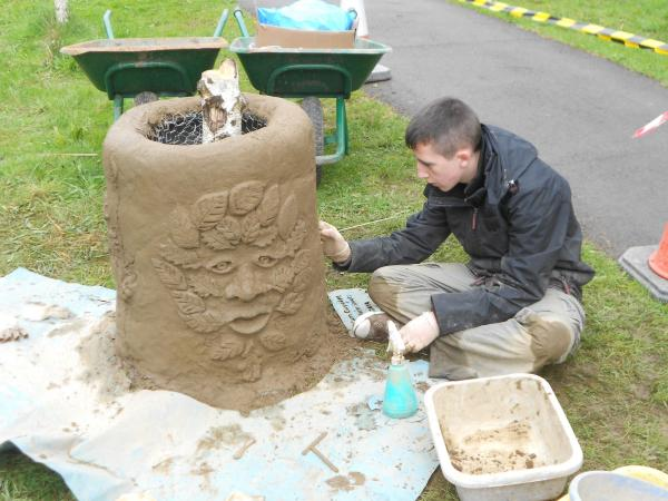 One of the Abercarn scouts building a giant plant pot at Cwmcar Forest Drive